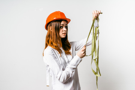 young discontented red-haired girl in a protective orange helmet holds a measuring tape in her hands