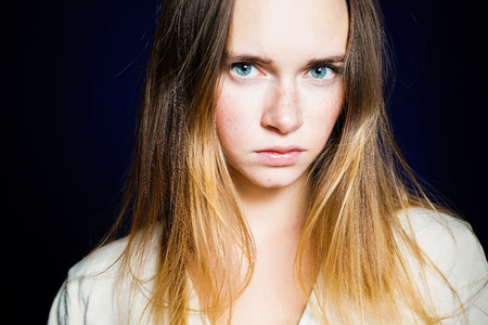sad young blue-eyed girl with light long hair, in a white jacket looks at the camera Stock Photo
