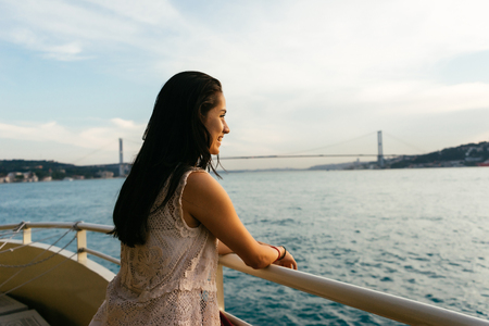 Happy cruise ship passenger outside on suite balcony enjoying luxury view of ocean and bridge in travel destination during summer. Beautiful Latin woman.
