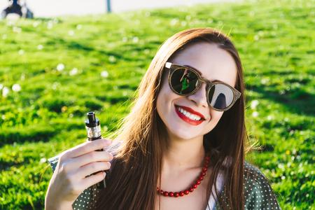 Moda feliz sonriente Mujer en gafas de sol fumando vape en la calle, humo