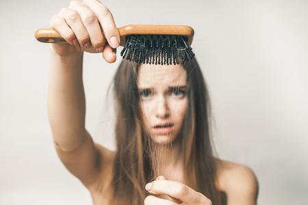 Woman with lost hair on comb,problems,white background