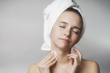 Woman removes cosmetics with cotton swab,cleaning face Stock Photo