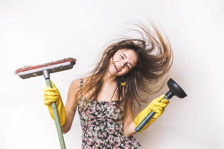 Joyful woman cleaning isolated on white,in yellow rubber gloves, holds a plunger and a brush