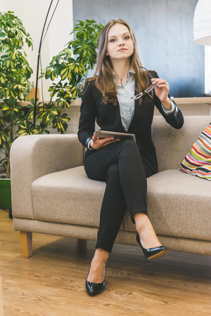 successful young woman in black trouser suit is sitting on sofa in office, holding glasses and tablet in hands