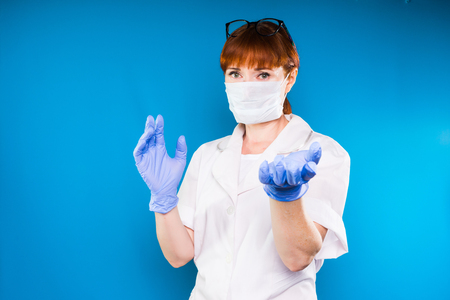 adult red-haired female doctor in white protective medical mask and lab coat posing