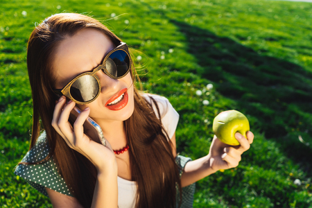 disgusted: Disgusted face woman use smartphone,holds in hands a green apple, sits on green grass Stock Photo