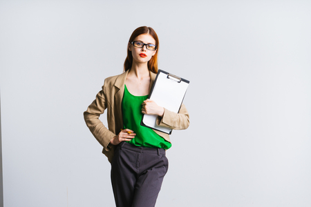 a serious girl in glasses and with bright lipstick on her lips looks at the camera and holds a folder in her hands, isolated Stock Photo
