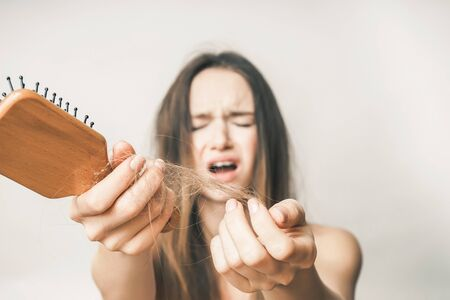 Lost hairs on comb close up,she is very sad, on a white background Stock Photo