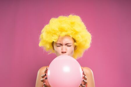 frightened young girl in a yellow clown wig inflates a pink balloon and is afraid that it will burst Banco de Imagens