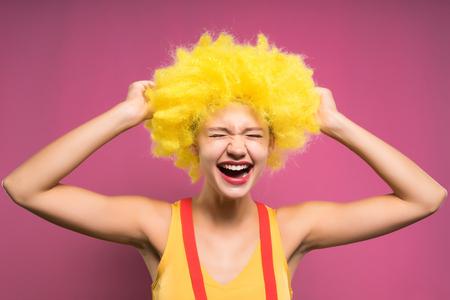 Jeune fille drôle dans une perruque de clown jaune rit, sur un fond rose Banque d'images - 89726151