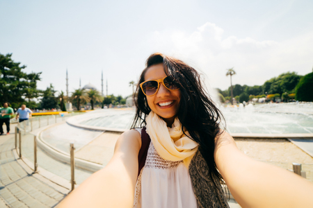 Happy girl traveler makes a photo of herself,in sunglasses, smiling Фото со стока