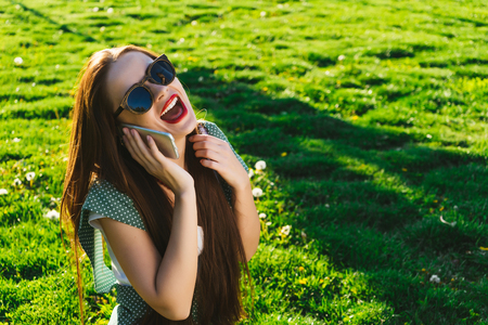 Happy smiling woman got good news,laughs, sits on the green grass