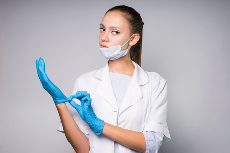 serious young woman doctor in white protective medical mask, dressing gown, putting on blue gloves