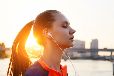 young sporty girl listening to music on headphones, by the river at sunset