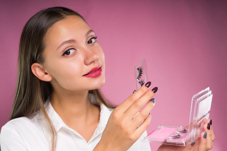 beautiful attractive girl in white shirt holds in hands packing of false eyelashes
