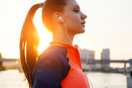 sports fitness girl listening to music in white headphones, in the sun Stock Photo
