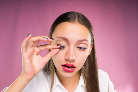 A young girl lays an eyelash overlay