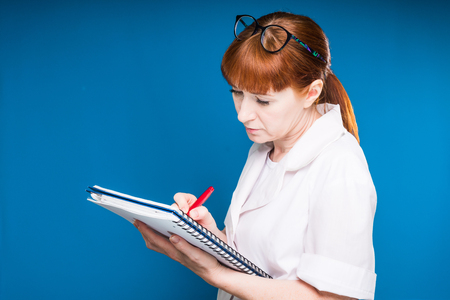 red-haired female nurse writes patient data to her journal, isolated on blue background Stock Photo