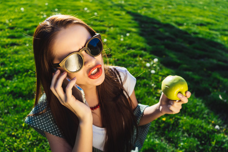 Angry woman speaking with mobile,holds an apple in his hand, sits on the green grass in the park