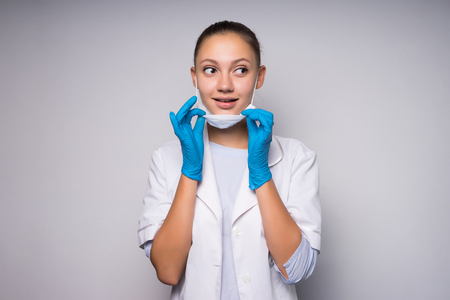 lovely young woman doctor in white protective mask and bathrobe smiling, looking away