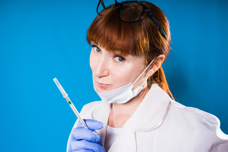 a nurse in a mask holds a syringe in his hands and is about to give a shot and looks into the camera sarcastically, isolated