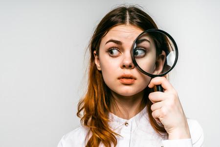 roodharig meisje op zoek in meer magnifier aan de zijkant, geïsoleerd op een witte achtergrond Stockfoto