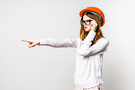 a girl in a white shirt and in an orange construction helmet and wearing glasses points her finger at something, isolated Stock Photo