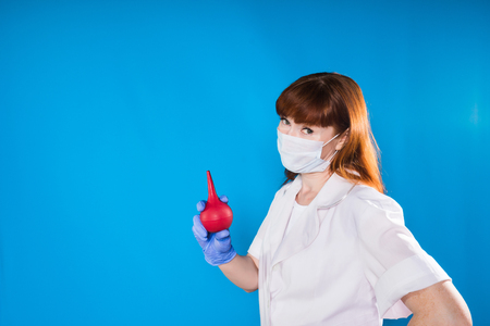red-haired nurse in a mask holds an enema and looks into the camera, isolated