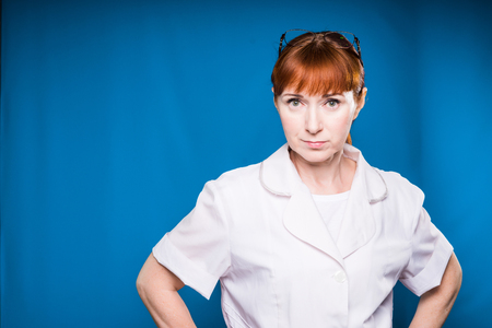 redhead nurse strictly looking into the camera, isolated on a blue background