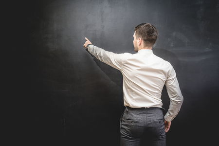 modern successful male construction builder in a white shirt points his finger on the chalkboard Stock Photo