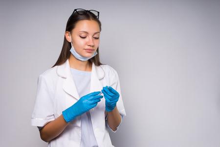 vertrouwen jonge vrouw arts in witte medische badjas en blauwe siliconen handschoenen houdt een spuit in handen Stockfoto