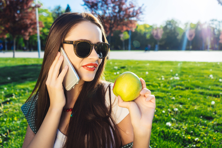 Positive woman smiling and enjoying sun,in glasses,talking on the phone and holding a green apple in his hand