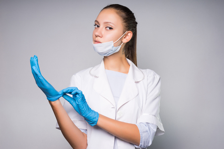 intelligent serious girl doctor in white medical dressing gown puts on blue silicone gloves on hands