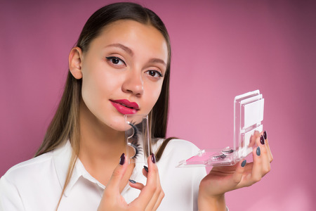 young beautiful girl in white shirt holds in hand false eyelashes, on pink background, looks at camera