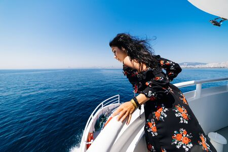 Surprised woman looking to the sea on yacht,in a stylish black dress