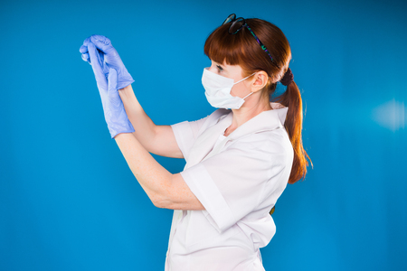 adult red-haired woman doctor in white protective mask and medical gown removes blue gloves from hands