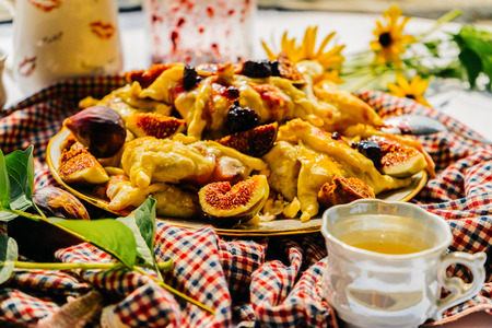checkered tablecloth and a plate with hot fragrant pastry and sweet figs, yellow flowers lie on the background, a mug with tea