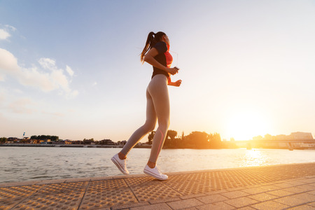 sports fitness girl in gray leggings running around the river in the sun