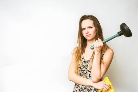 the dissatisfied young girl holds in her hands the plunger and yellow rubber gloves, does not want to do cleaning