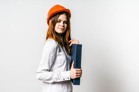 smiling young girl in a white shirt wearing an orange protective helmet on her head holding a folder with documents Stock Photo