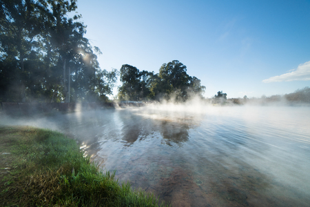 Fog rises over the river, against the blue sky