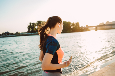 A sports girl with a phone in her hands performs an evening run Stock Photo