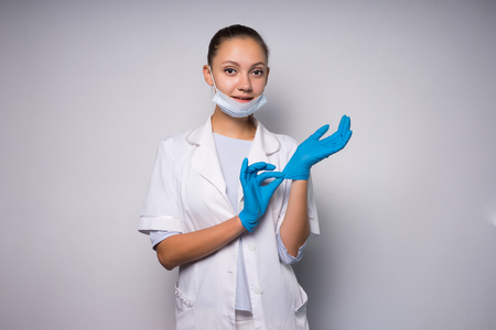 smiling young woman doctor in white protective mask and medical dressing gown, putting on gloves