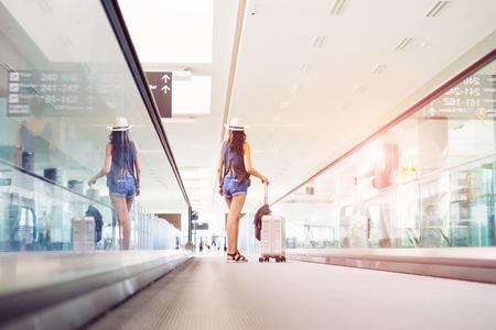 젊은여자가 손 짐, 가방 국제 공항 터미널에서 에스컬레이터를 들고. 휴가 여행자