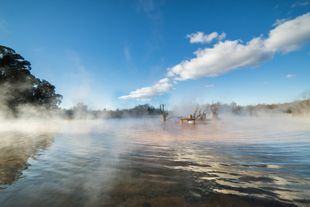 The mist rises over the river, white clouds on the blue sky