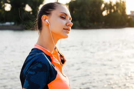 young athletic girl enjoys good weather, after training, eyes are closed, listening to music on headphones