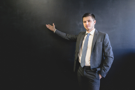 confident successful young business man in suit shows something on