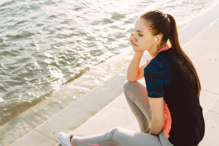 A sports young girl is resting by the river Stock Photo