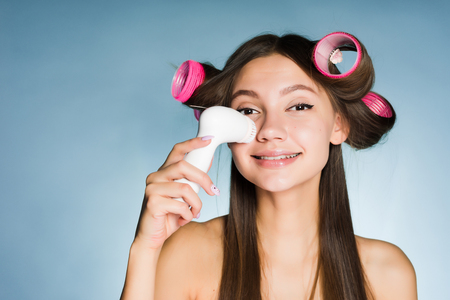 a smiling young girl wants to be beautiful, makes a hairstyle with a large curler, cleans her face with an electric brush