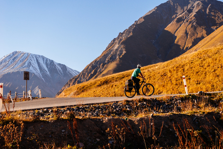 on the background of high Caucasian mountains on the road rides a bicyclist in the helmet Stock Photo